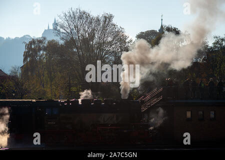 Wernigerode, Germany. 30th Oct, 2019. A steam locomotive of the Harzer Schmalspurbahnen (HSB) is located in the station Wernigerode. In the background you can see the castle Wernigerode. The company changed from summer to winter timetable on 26 October. Credit: Klaus-Dietmar Gabbert/dpa-Zentralbild/ZB/dpa/Alamy Live News - Stock Photo