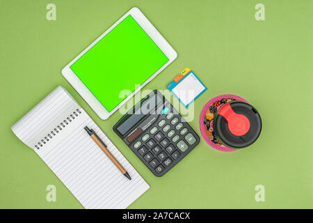 Green screen tablet, office school stationery, reusable coffee cup on green background. Flat lay top down view. Business Objects Technology concept. - Stock Photo