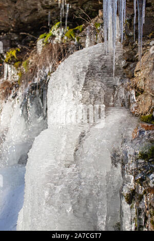 Rocks under ice layers,  phantasmagoric ice shapes, frozen leaves, grass. Czech mountains. - Stock Photo