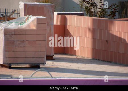 hollow brick wall unter construction and stack of clay blocks, hollow clay blocks  wall on construction site - Stock Photo