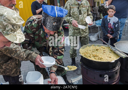 Dnipro, Ukraine - September 29, 2018: Ukrainian Cossacks lays out cooked porridge in plates during holiday in honor of 100th anniversary of Dnipro Aca - Stock Photo