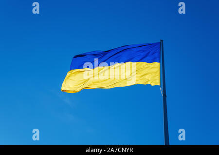 Ukrainian flag flying on a flagpole in against the blue sky on a warm summer day - Stock Photo