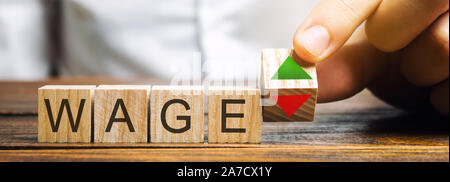 Wooden blocks with the word Wage and up and down arrows. The concept of unstable wages. Business and finance. Income, salary, revenue - Stock Photo
