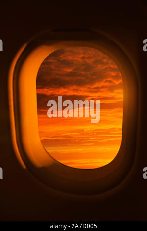 View out of an airplane window of a bright red sunset - Stock Photo