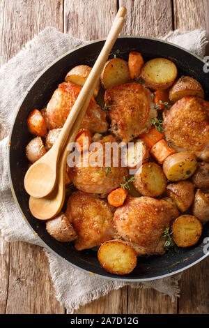 Rustic style chicken thighs baked with potatoes, carrots, thyme in wine sauce close-up in a pan on the table. Vertical top view from above