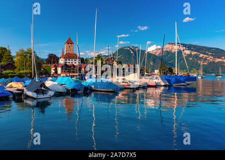 Spiez Church and Castle on the shore of Lake Thun with yachts in the Swiss canton of Bern at sunset, Spiez, Switzerland. - Stock Photo