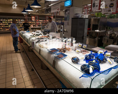 Refrigerated iced counter with fresh fish, seafood and mussels and with price labels in an Italian supermarket with seller behind the bar - Stock Photo