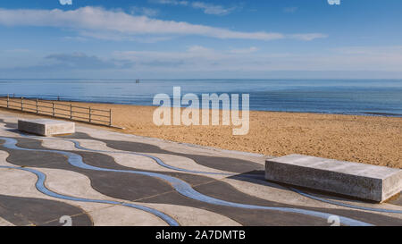 Ramsgate beach main sands and wave patterned concrete promenade  on a clear blue winter day