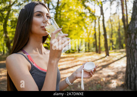 Beautiful woman enjoying her lemon water outside - Stock Photo