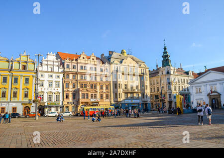 Pilsen, Czech Republic - Oct 28, 2019: People on the main square, Republic Square, in Plzen, Bohemia, Czechia, Historical buildings in the background. Old town, sunny day. Daily life, city streets. - Stock Photo