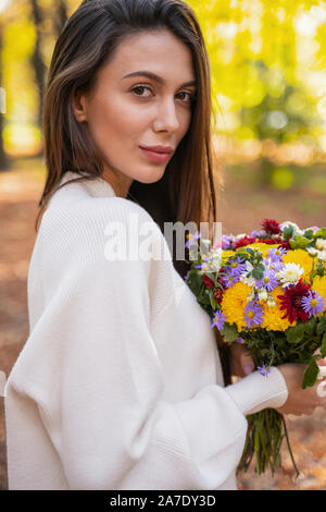 Gorgeous young woman walking during her date - Stock Photo