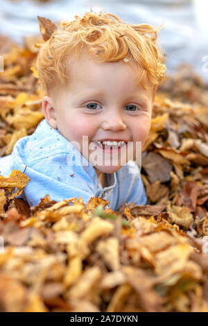 Portrait of happy little red hair boy lying in the middle of colorful autumn leaves