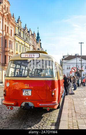 Pilsen, Czech Republic - Oct 28, 2019: Vintage red bus on the main square in Plzen, Bohemia, Czechia. Part of the national holiday celebration program. Historical center. Old bus, transportation. - Stock Photo