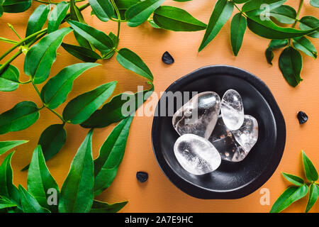 Clear Quartz with Jasmine Leaves on Golden Background - Stock Photo