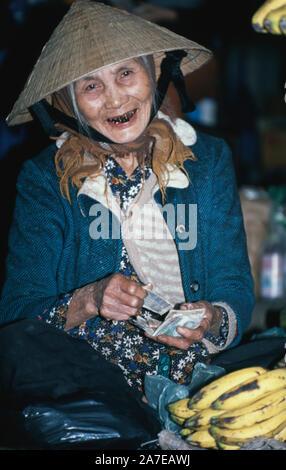 An elderly Vietnamese fruit vendor counts the day's takings in the Mekong Delta, Vietnam. - Stock Photo