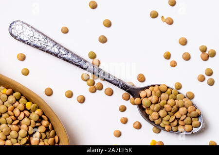 Lentils in Decorative Metal Spoon with random scattered seed on white background. - Stock Photo