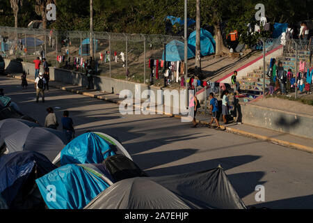 Matamoros, Mexico, 01 November 2019, migrants are seen on the road just south of the Rio Grande only a few meters from the border with the United States.  Hundreds of tents are erected with washing hanging out to dry on the fence.  Around 2000 refugees are currently living in tents next to the International Bridge that connects the Mexican city of Matamoros with the US city of Brownsville.    Credit: Lexie Harrison-Cripps/Alamy Live News - Stock Photo
