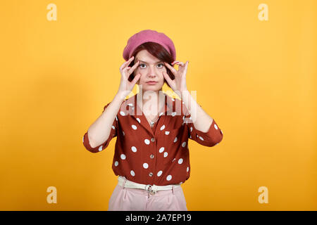 young girl wearing redshirt in white polka dot trying to open eyes with fingers - Stock Photo