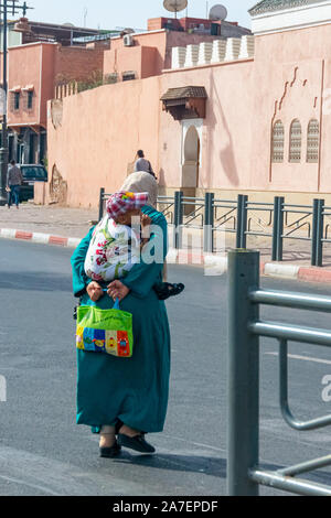 Arab woman with child behind her back in the city of Marrakech. Morocco October 2019 - Stock Photo