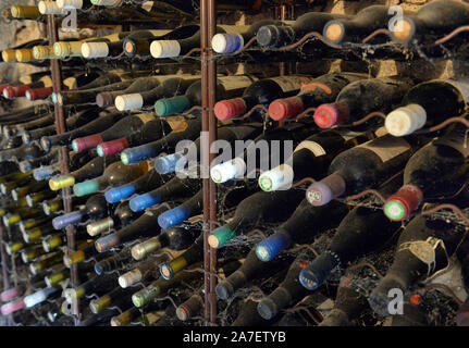 dusty wine bottles in a wine cellar. Wine bottles stacked up in old wine cellar close-up background. Underground wine cellars - Stock Photo