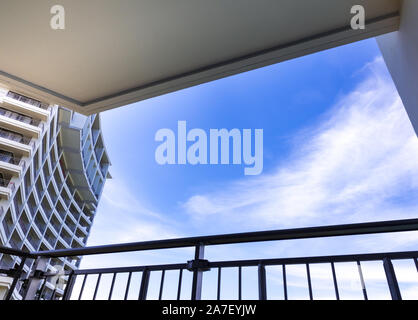 High-rise building and blue sky view from balcony - Stock Photo