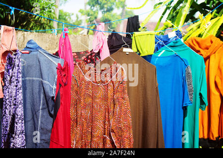 Colorful Clothes laundry on hanger hanging in rope in front yard - Stock Photo