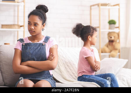 African american sisters sitting back to back on couch - Stock Photo