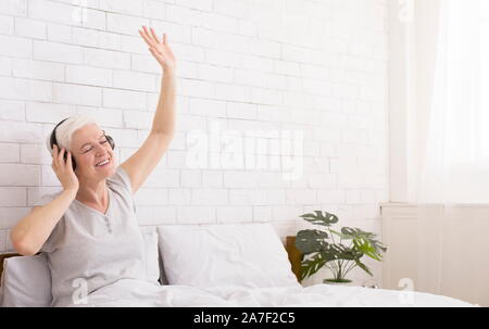 Playful senior lady in headphones listening to music in bed - Stock Photo
