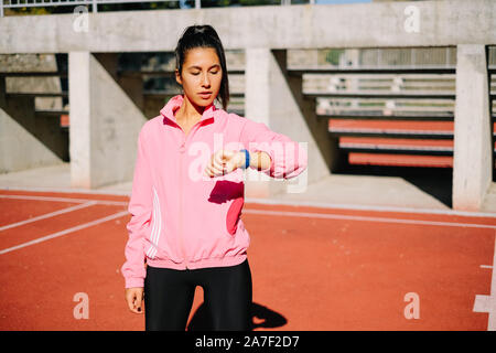 Active girl uses fitness tracker smart watch - Stock Photo