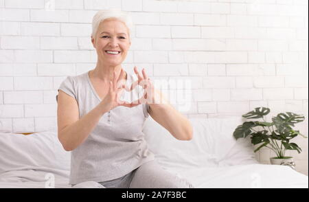 Cute senior woman making heart shape with her hands and fingers - Stock Photo