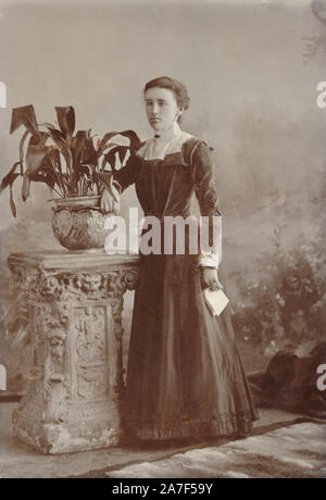 Late Victorian or early Edwardian cabinet photo card portrait of young Edwardian woman holding a letter and wearing a sombre, dark dress, posing next to potted plant - an aspidistra which were popular plants at this time. circa 1901, Truro, Cornwall, U.K. - Stock Photo