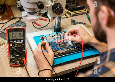 Young repairman holding small soldering-irons while working with tiny details - Stock Photo