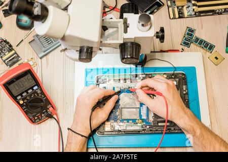 Overview of hands of professional repairman with soldering-irons during work - Stock Photo