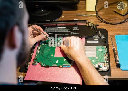 Tweezers in hands of repairman over demounted gadget working with tiny details - Stock Photo