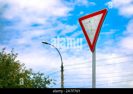Give way road sign against cloudy sky. - Stock Photo