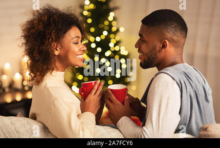 Excited black couple drinking coffee on Christmas eve - Stock Photo