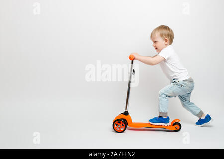 Happy Toddler child in jeans rides an orange scooter on a white background in the studio. Concept for advertising children's toys with space for text. - Stock Photo