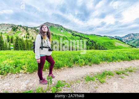 Albion Basin, Utah summer with woman standing in sweater with backpack and camera looking at landscape view on meadows trail in Wasatch mountains wild - Stock Photo