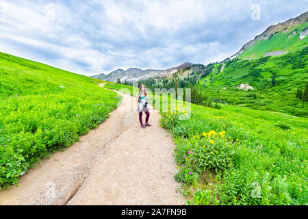 Albion Basin, Utah summer with wide angle of woman standing on steep road landscape view on meadows trail in Wasatch mountains wildflowers - Stock Photo