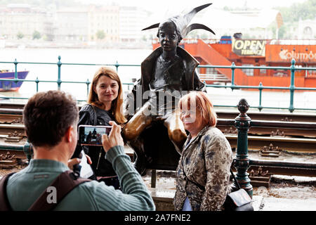 Budapest, Hungary - May 27, 2019: tourists photograph themselves together with famous statue - Stock Photo