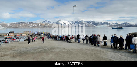 Passengers from P&O cruise ship Aurora queuing to return to their ship, seen anchored in the Kongsfjorden at Ny Alesund. - Stock Photo