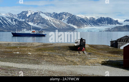 An old mining train on the shore of the Kongsfjorden at Ny Alesund on the island of Spitsbergen, and mv Plancius research vessel. - Stock Photo