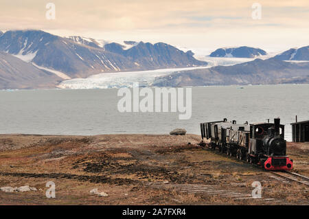 An old mining train on the shore of the Kongsfjorden at Ny Alesund on the island of Spitsbergen. - Stock Photo