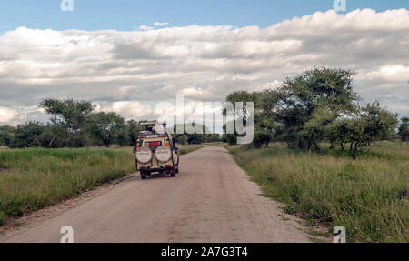 AMBOSELI, Kenya - MAY 2014. Tourist in jeep safari in the road of National Park of Kenya. They are traying see animals. - Stock Photo