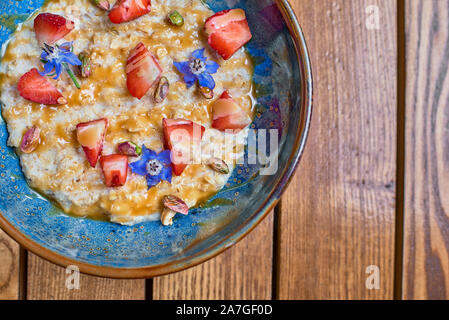 Granola for breakfast with berries and caramel. Oatmeal flakes or granola with strawberries. The concept of diet, healthy eating and eating. Top view, - Stock Photo