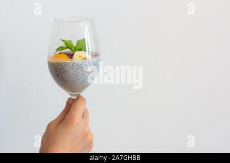 Young girl holding a glass of chia healthy food coconut pudding with banana, mango and dragon fruit in her hands. Healthy concept - Stock Photo