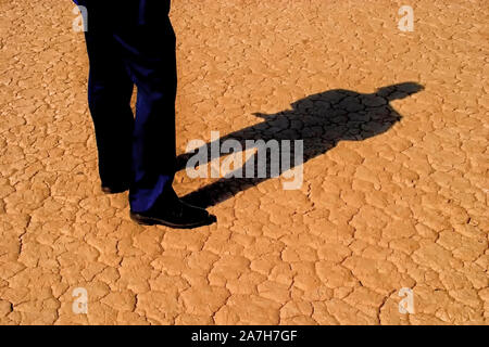 Man's legs in business slacks and full body shadow on cracked desert ground - Stock Photo
