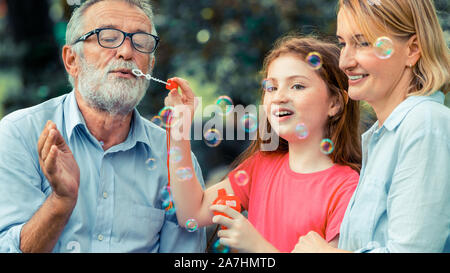 Happy family blows soap bubbles together while going vacation on weekend in the garden park in summer. Kid education and family activities concept. - Stock Photo
