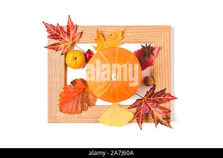 Picture frame with autumn leaves, quince and orange pumpkin. Creative thanksgiving day or halloween concept. flat lay - Stock Photo