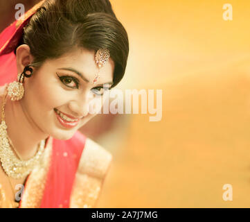 Stunning Indian bride dressed in Hindu red traditional wedding clothes sari embroidered with gold jewelry and a veil smiles tender with extra copy spa - Stock Photo